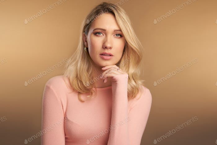 Studio portrait of blonde girl with green eyes and fair skin, pink sweater against a brown backdrop