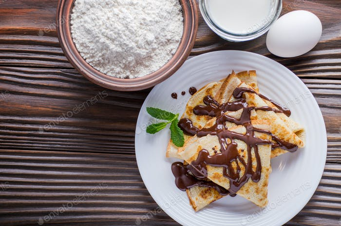 Flat lay French crepes with chocolate sauce walnuts eggs and flo