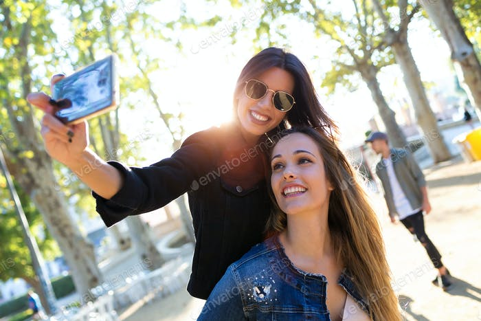 Beautiful young women taking photos with mobile phone in eat market in the street.
