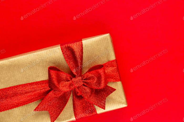 Draufsicht der angeordneten verpackten Weihnachtsgeschenkboxen mit Bändern auf roter Tischplatte.