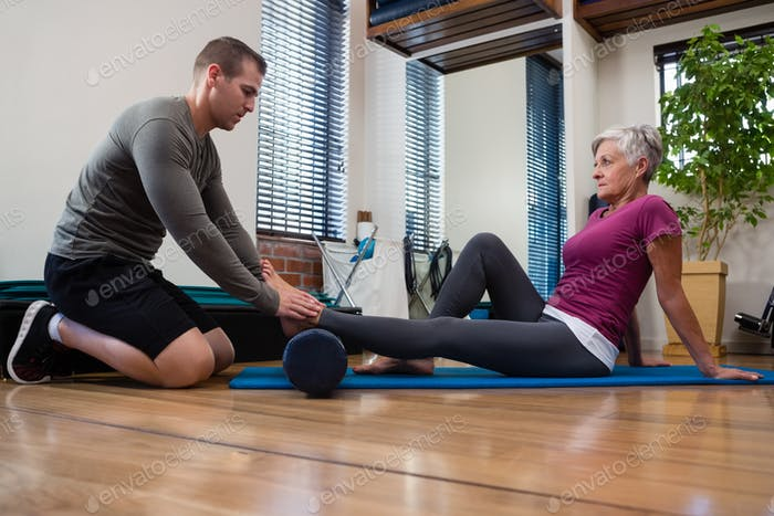 Physiotherapeut gibt Physiotherapie des Beines an ältere Patienten