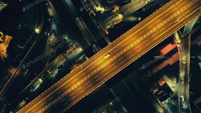 Top down of traffic road at night illuminate aerial. Metropolis cityscape with modern buildings