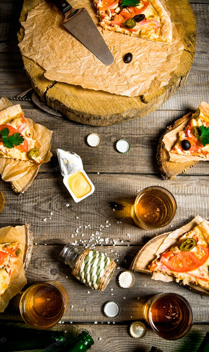 Pizza and beer for four people. On a wooden table.