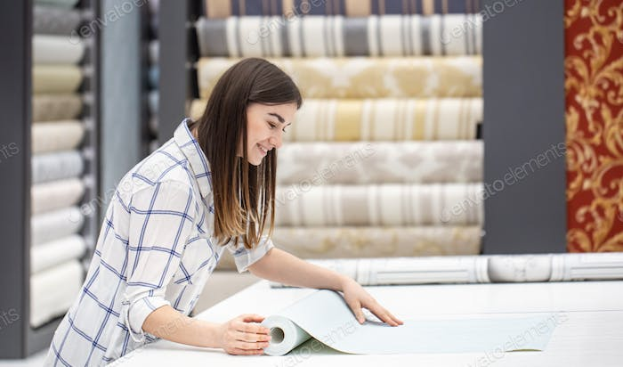 A young woman in a store chooses Wallpaper for her home.