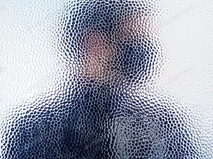 Mann in schwarzer Gesichtsmaske hinter geschlossener Tür Glas