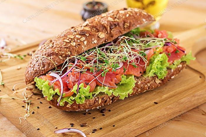 Lachs-Sandwich - smorrebrod mit Käsecreme und Mikrogrün auf Holztisch.