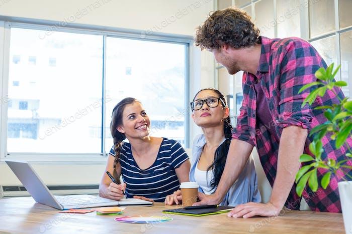 Lächelnde Partner arbeiten zusammen auf Laptop und Digitizer im Büro