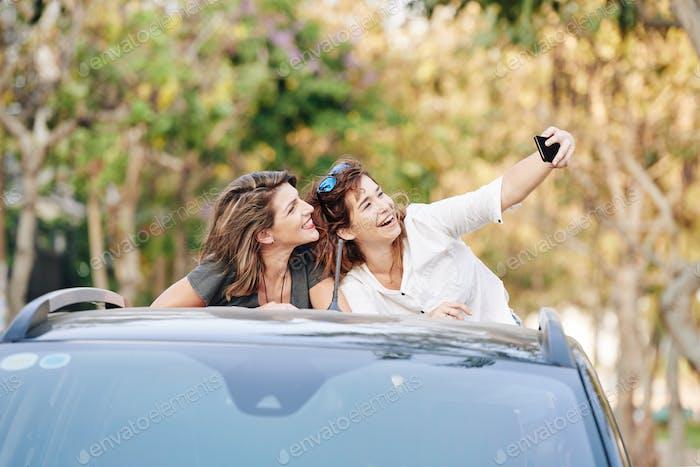 Cheerful friends taking selfie in back of pickup truck