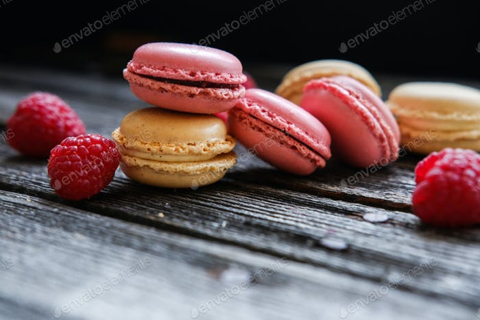 Colorful French macarons with raspberries on a table