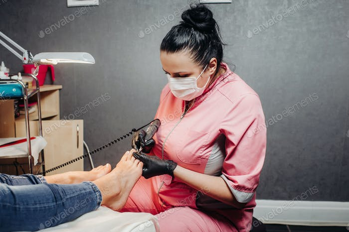 The master makes a pedicure in the beauty salon. The girl in a blue mask and gloves makes cosmetic