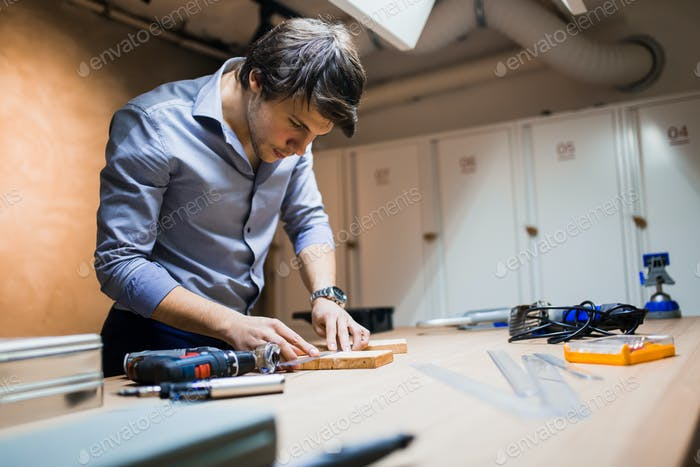 Joiner working and designing on workbench