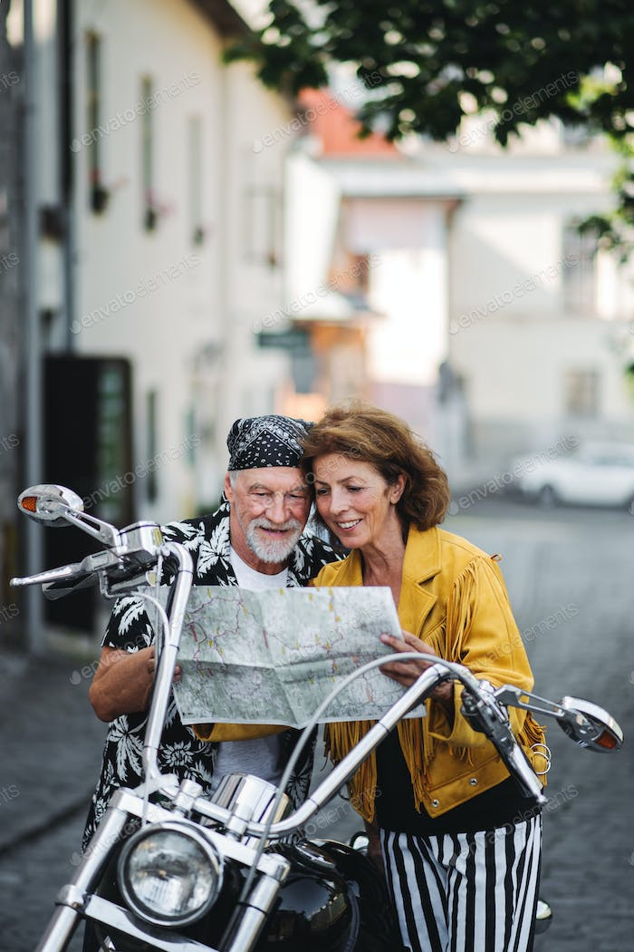 A cheerful senior couple travellers with motorbike in town, using map.