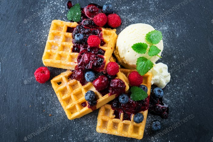Waffles with ice cream and hot fruits sauce