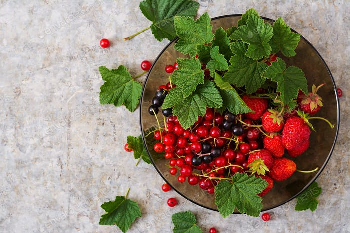 Plate with fresh berries (strawberries and currants) on grey background. Top view