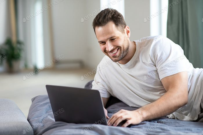 Happy Freelancer Man Using Laptop Working Online Lying In Bed