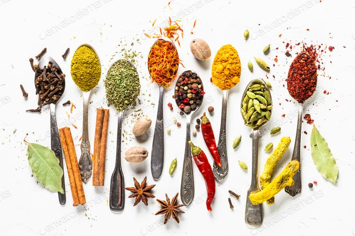Set of various spices in spoons on white