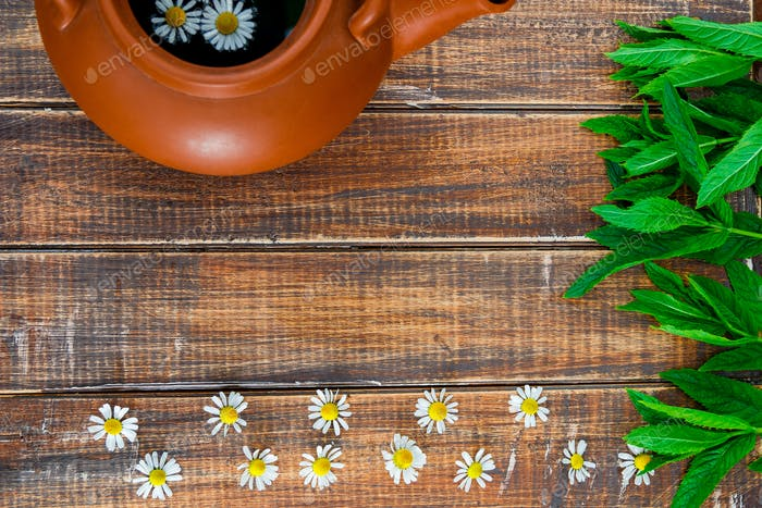 brown teapot with tea near flower of chamomile and fresh mint on wooden background.