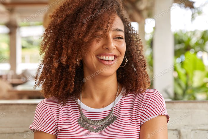 Headshot of funny black woman with curly hair, laughs at good joke, has toothy smile, shows white pe