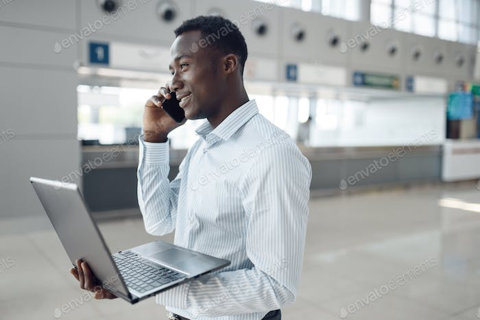 Businessman with phone negotiates in car showroom
