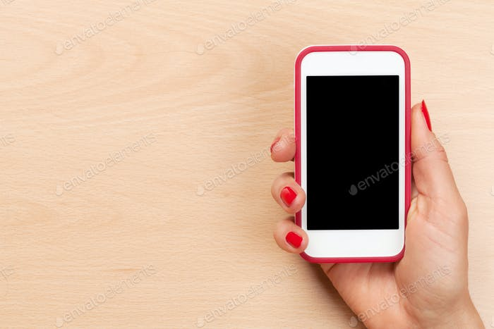 Female hand holding a smartphone above desk table