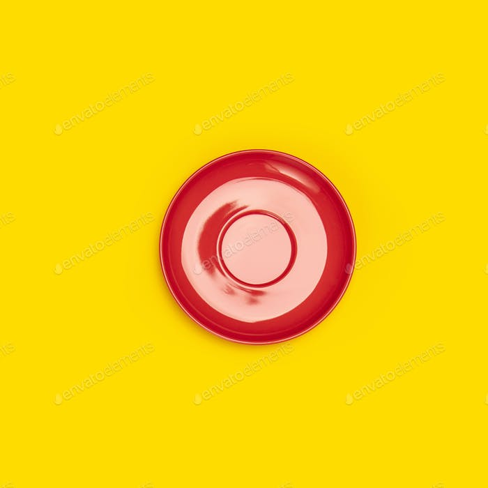 Top view of red ceramic plate saucer on yellow background
