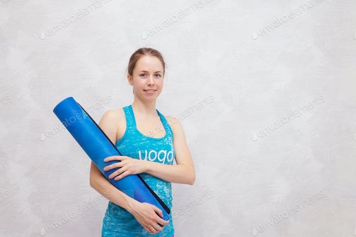 Woman yoga portrait with a mat.