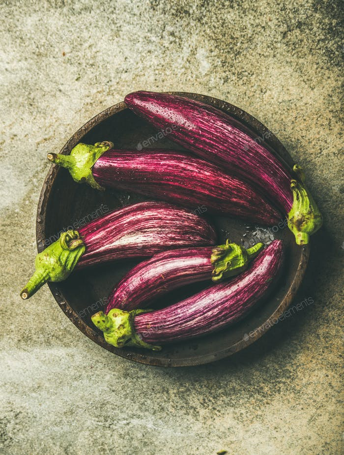 Flat-lay of fresh raw Fall harvest purple eggplants or aubergines