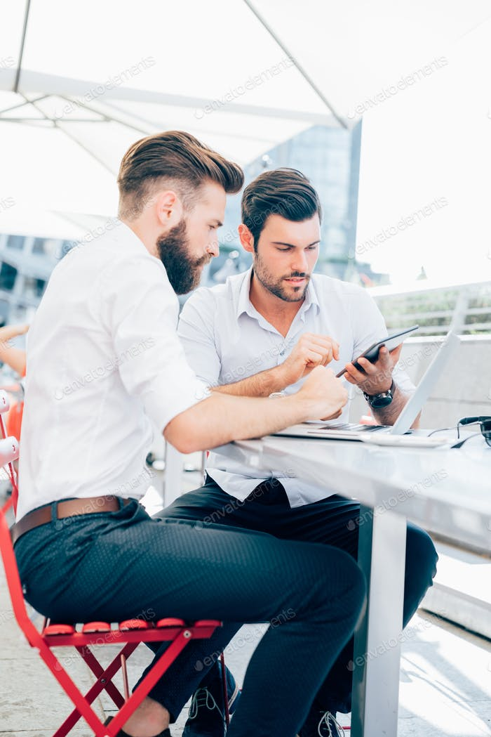 Two young contemporary businessmen working outdoor