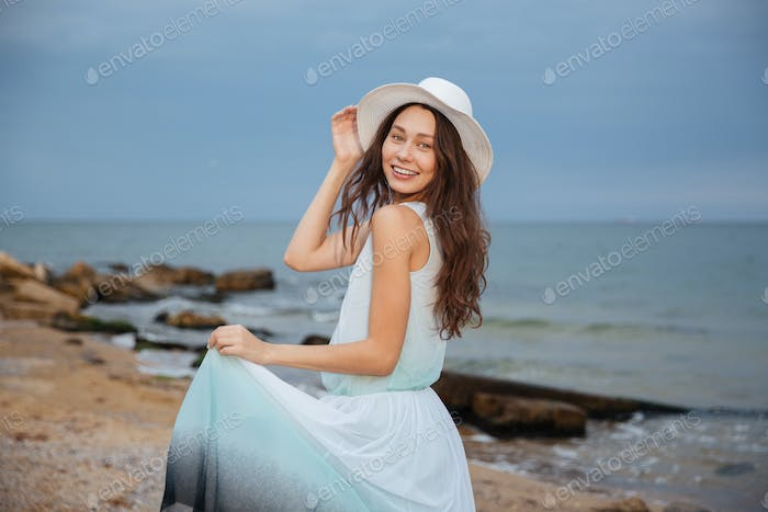 Happy attractive young woman walking on the beach