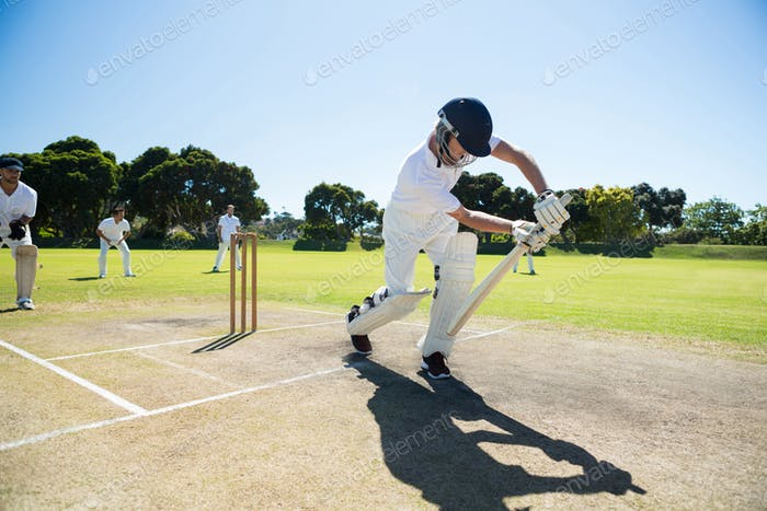 Young man playing cricket at field against clear sky