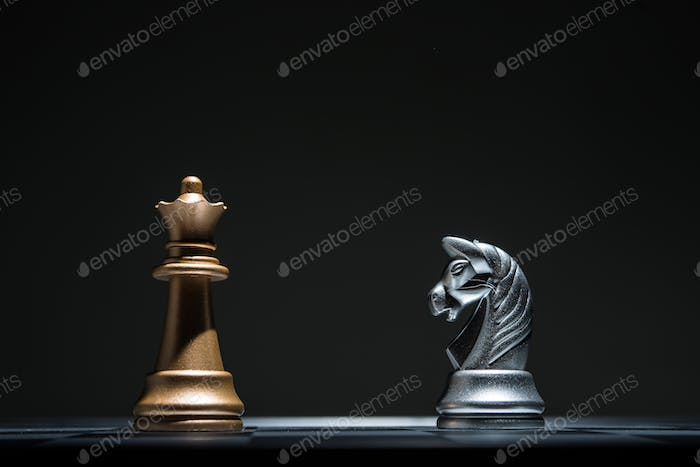 Chessboard with chess pieces on black background. Leader business concept.