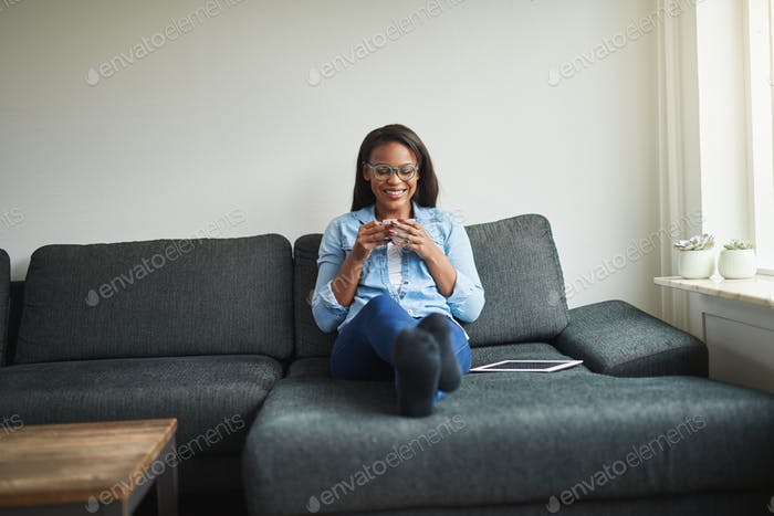 Smiling African woman relaxing on her sofa with a coffee
