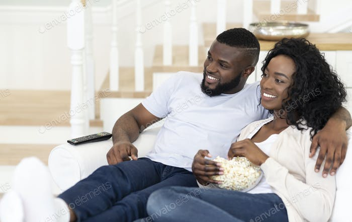 Husband and wife sitting on couch with popcorn, watching tv