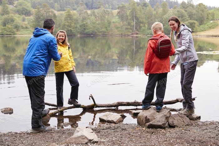 Junge Familie spielt mit ihren Kindern am Ufer eines Sees, Lake District, UK
