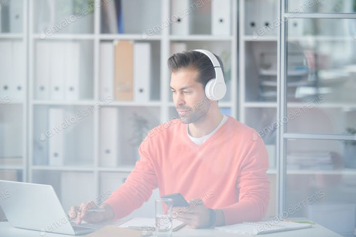 Casual young businessman in headphones using modern gadgets