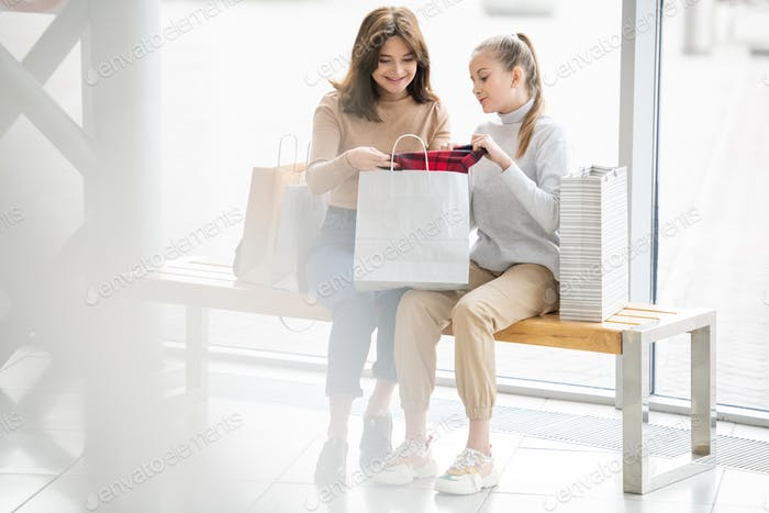 Pretty young woman and girl looking at new flannel in paperbag