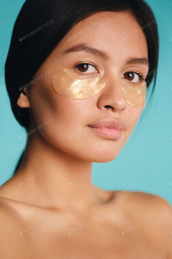 Close up attractive Asian girl with patches under eyes confidently looking in camera