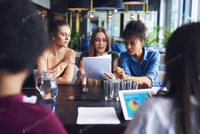 Three businesswomen analyzing the documents during business meeting