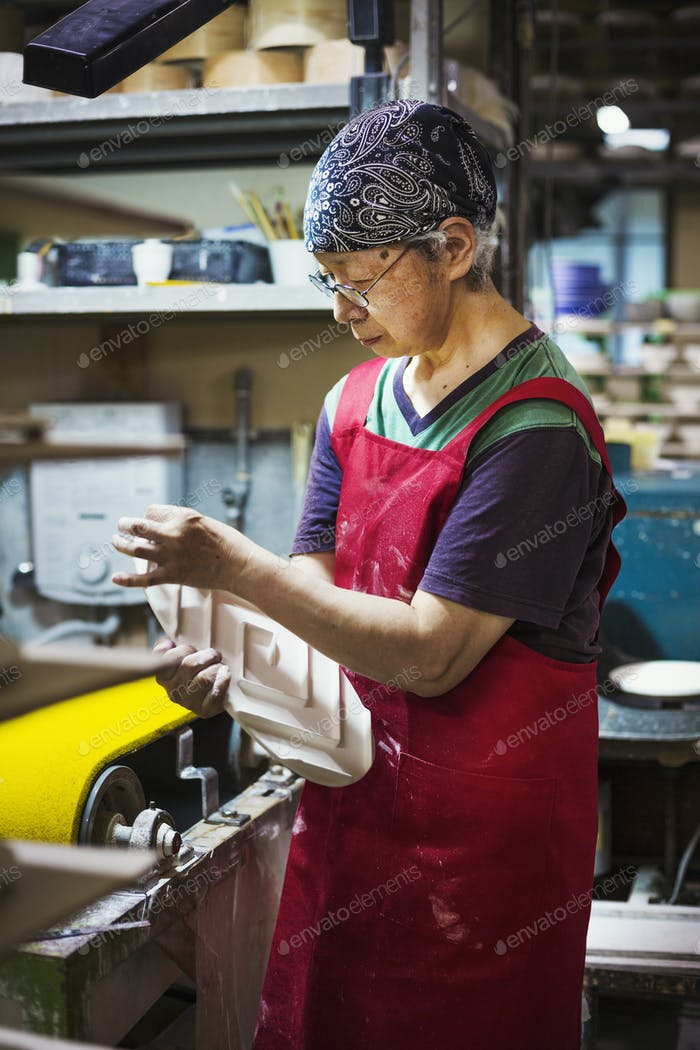 Woman working in a Japanese porcelain workshop, wearing apron, holding white porcelain object.