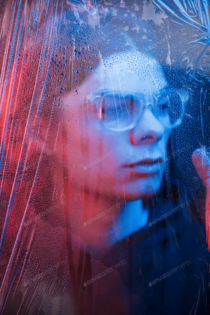 Studio shot in dark studio with neon light. Portrait of serious man behind the wet glass