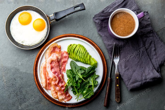 Ketogenic diet breakfast. fried egg, bacon and avocado, spinach and bulletproof coffee