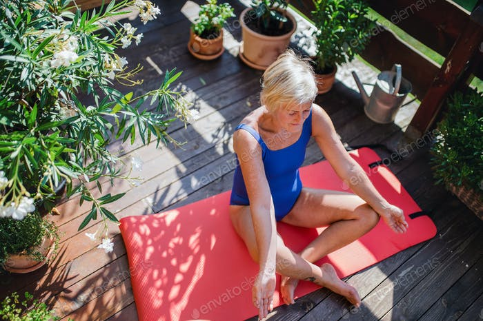 A senior woman sitting outdoors on a terrace in summer, doing yoga exercise.