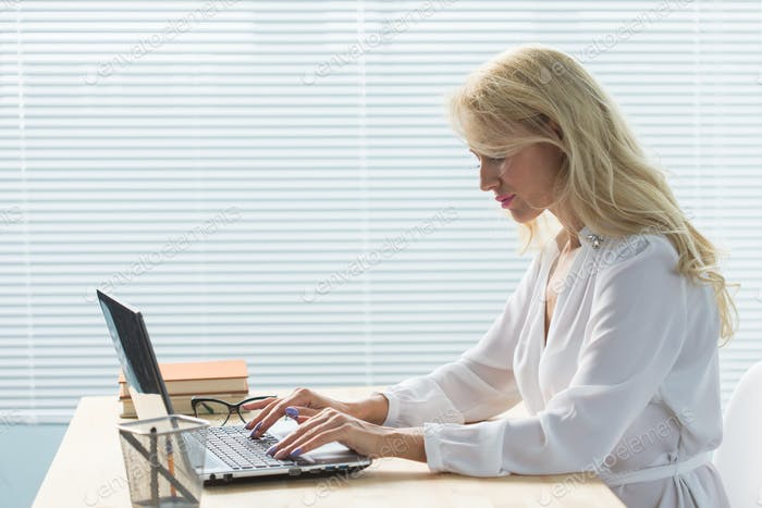 Working, business, technology and people concept - young woman working in office with laptop and