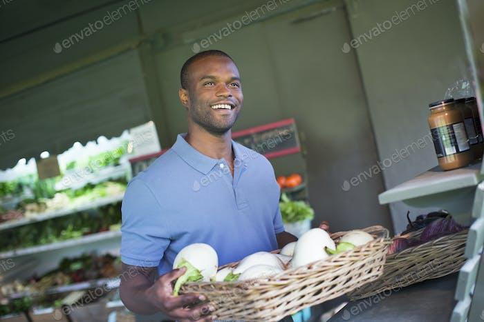 Ein Bio-Obst- und Gemüsebauernhof. Ein Mann, der Gemüse sortiert.