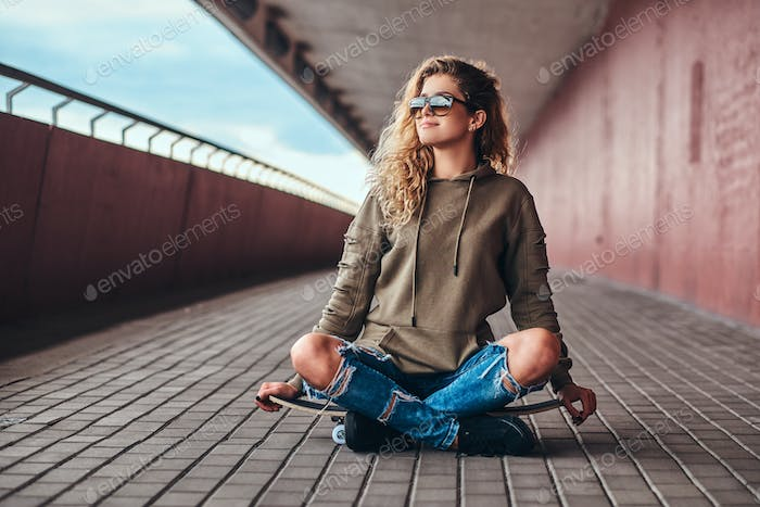 Young woman sitting on a skateboard with crossed legs on bridge footway.