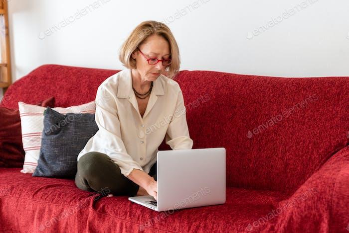 Elegante reife Frau mit Computer zu Hause