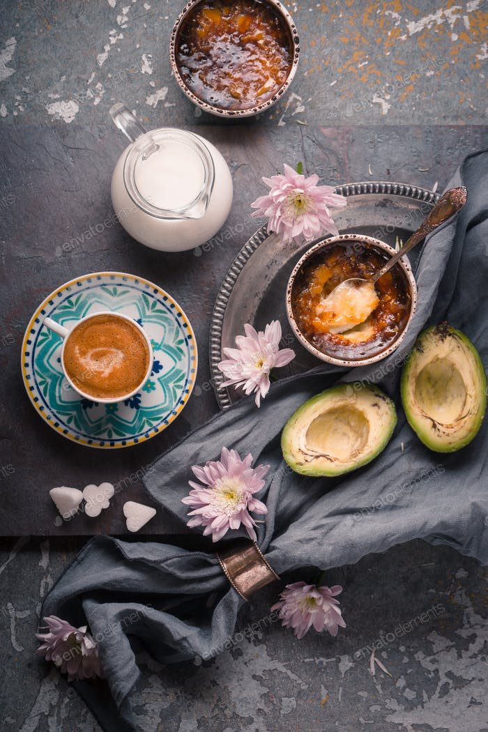Still life with Catalan cream , avocado and cup of coffee on the stone background