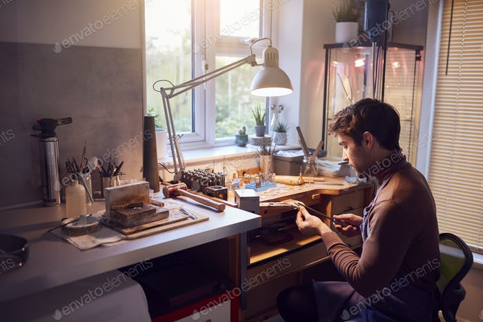 Male Jeweller Wearing Apron At Bench Working In Studio