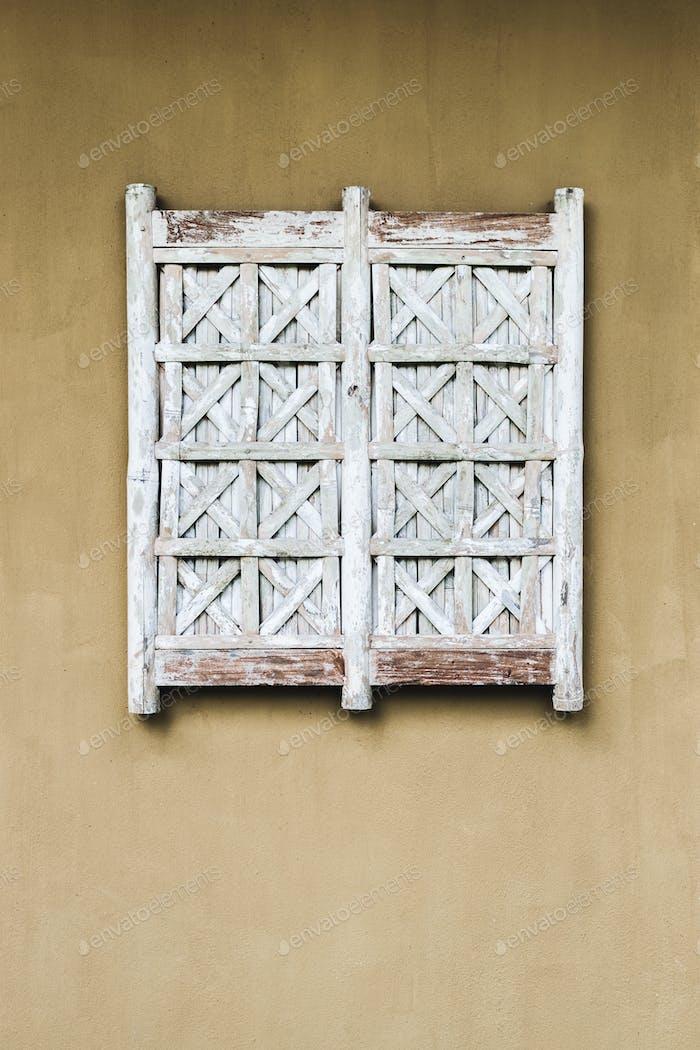 Das  Fenster an der orangefarbenen Wand ist mit weißen Korbläden bedeckt. Äußeres im Bali-Stil