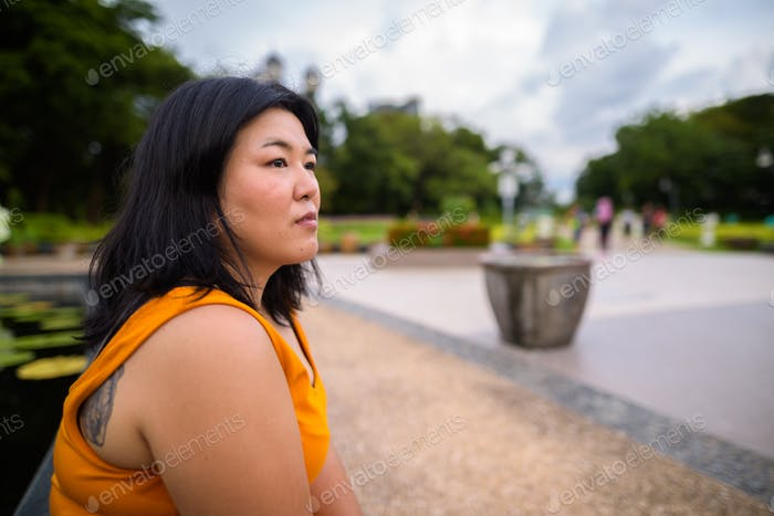 Profile view of overweight Asian woman sitting and thinking in park